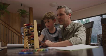 abacus : Low angle side view of a Caucasian man and his young son at home in the living room, sitting at a table talking and using an abacus together on the table in front of them, slow motion