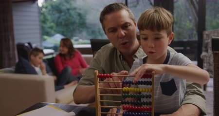 abaco : Front view of a Caucasian man and his young son at home in the living room, sitting at a table talking, and doing schoolwork together, the boy using an abacus on the table in front of them, his brother and mother sitting on a sofa in the background, slow  Archivo de Video