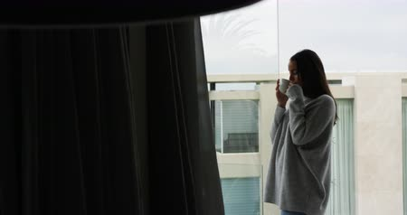 generation z : Side view of young woman enjoying time off, standing on a balcony and drinking coffee with a building in the background, slow motion