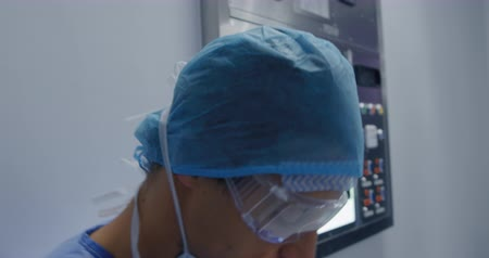 手順 : Side view close up of a caucasian surgeon male healthcare worker in a hospital oprating theatre, leaning against a wall and talking a break