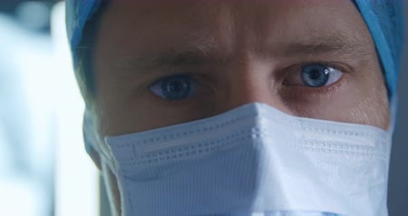 surgery theatre : Portrait close up of a caucasian surgeon male healthcare worker in a hospital operating theatre, wearing a surgical mask and looking to camera