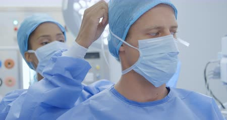 trabalho em equipe : Front view close up of a surgeon caucasian male and female healthcare worker in a hospital, preparing for an operation, the woman tying a surgical mask for the man, both wearing scrubs and caps Vídeos