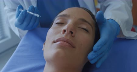 aguja hipodermica : Front view close up of a Caucasian female patient on the operating table in a clinic receiving a injections in her face from a cosmetic surgeon, slow motion Archivo de Video