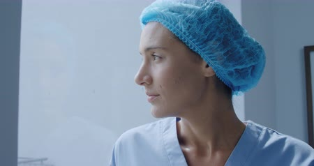 arbustos : Side view close up of a Caucasian female healthcare worker in a hospital, wearing scrubs and a cap, looking away, slow motion