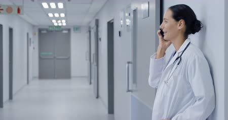 szpital : Side view of a happy Caucasian female doctor wearing a lab coat and stethoscope standing in a hospital corridor, talking on a smartphone and smiling