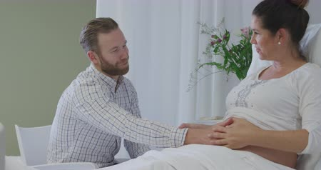 natal : Side view of an expectant Caucasian couple in a hospital ward, the man sitting beside the bed, both their hands on her belly, and talking with his pregnant wife, who is sitting up in bed and smiling, a vase of flowers on the table beside her