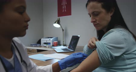 natal : Side view of a mixed race female healthcare professional at a hospital, sitting and giving an injection to a pregnant Caucasian woman during a pre-natal consultation
