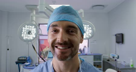 surgery theatre : Portrait close up of a caucasian surgeon male healthcare professional with a beard in a hospital operating theatre, wearing a surgical cap, smiling to camera, slow motion