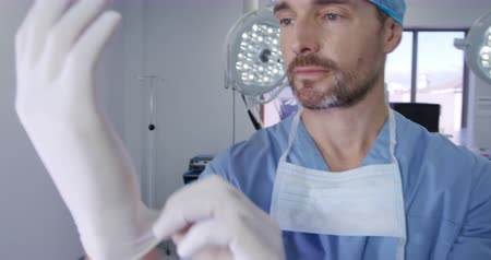 surgery theatre : Portrait close up of a caucasian male surgeon healthcare professional in a hospital operating theatre putting on surgical gloves in a hospital operating theatre and smiling to camera Stock Footage