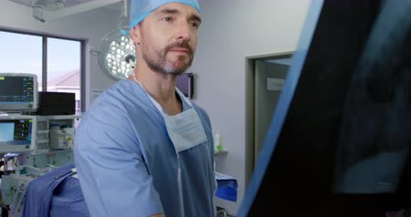 chirurgia : Side view close up of a caucasian surgeon male healthcare professional with a beard in a hospital operating theatre wearing a surgical cap, looking at an x ray, slow motion Wideo