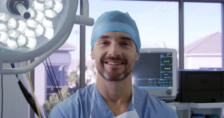arbustos : Portrait close up of a caucasian surgeon male healthcare professional in a hospital operating theatre wearing a surgical cap and scrubs in a hospital operating theatre, smiling to camera