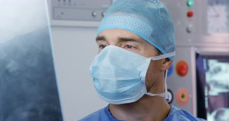 surgery theatre : Front view close up of a Caucasian male healthcare professional in a hospital operating theatre wearing a surgical cap and mask, looking at an x ray Stock Footage