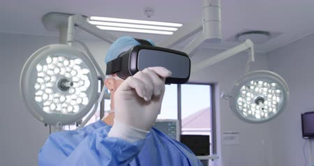 surgery theatre : Front view close up of a caucasian surgeon male healthcare professional at work in a hospital operating theatre wearing a surgical cap and mask and a vr headset, raising his hands in front of him, with medical equipment in the background, slow motionn Stock Footage