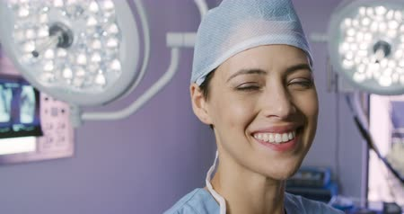 chirurgia : Portrait close up of a mixed race female healthcare professional in a hospital operating theatre, wearing scrubs and a surgical cap, looking to camera and smiling, with medical equipment in the background, slow motion Wideo