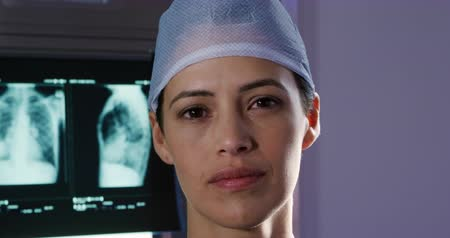 surgery theatre : Portrait close up of a mixed race female healthcare professional in a hospital operating theatre, wearing scrubs and a surgical cap, looking to camera, with medical x rays in the background