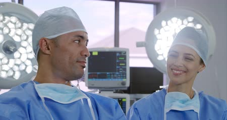 surgery theatre : Front view of a mixed race female and a mixed race male healthcare professional wearing surgical caps and gowns, with masks around their necks, in a hospital operating theatre, looking to camera smiling, and turning to smile at each other, slow motion Stock Footage