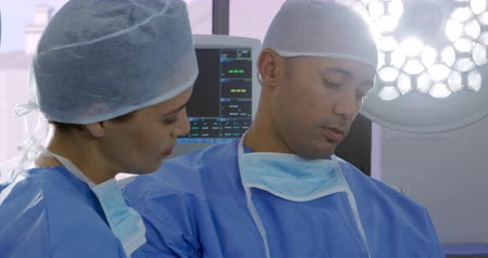 surgical mask : Side view of a mixed race female and a mixed race male healthcare professional wearing surgical caps and gowns, with masks around their necks, in a hospital operating theatre, having a discussion