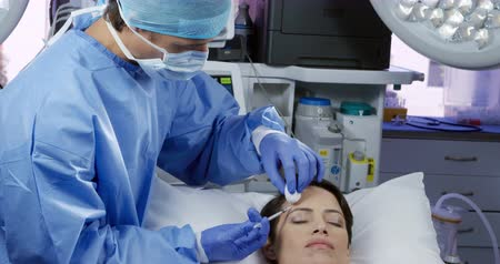 aguja hipodermica : Front view of a Caucasian female patient on the operating table in a clinic receiving injections to her forehead from a male cosmetic surgeon Archivo de Video