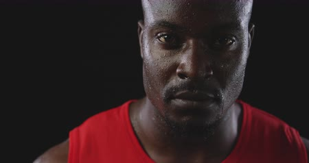 perspiring : Portrait close up of an African American male athlete sweating after a work out, looking to camera, slow motion, on black background