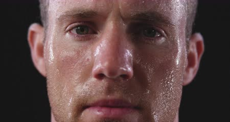 perspiring : Head shot of a Caucasian male athelete sweating after a work out, looking straight to camera, slow motion, on black background Stock Footage