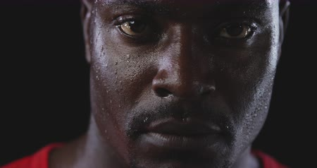 perspiring : Head shot of an African American male athlete sweating after a work out, looking to camera, slow motion, on black background