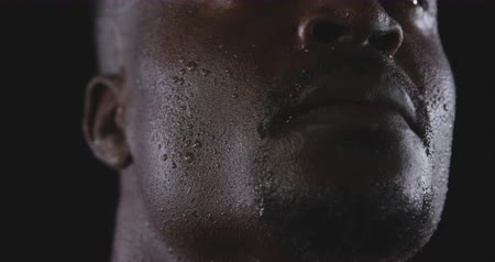 perspiring : Low angle head shot of an African American male athlete sweating after a work out, looking up, slow motion, on black background