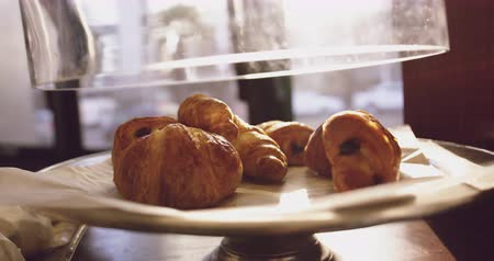 fedél : Glass lid being lifted off a plate of croissants at cafe at breakfast time, slow motion with light shining in Stock mozgókép