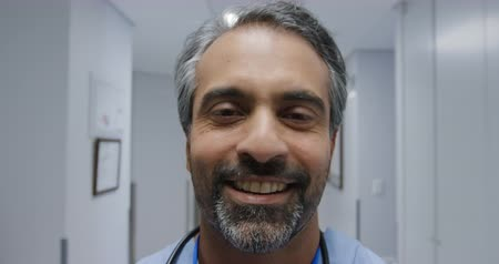 consulente : Portrait close up of a mixed race male healthcare professional with short hair and a beard smiling to camera in a hospital corridor Filmati Stock