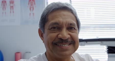 bigode : Portrait close up of a senior mixed race man looking straight to camera and smiling in a hospital examination room Stock Footage