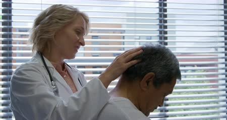 consulente : Side view of a senior mixed race male patient sitting while a Caucasian female doctor wearing a lab coat stands behind him touching his head with her hand, slow motion Filmati Stock