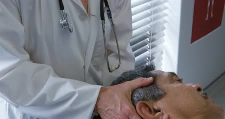opção : Front view of a senior mixed race male patient lying on a couch while a Caucasian female doctor wearing a lab coat holds his head and moves it from side to side during a physiotherapy session Stock Footage