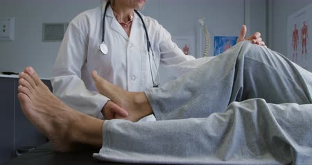 four legs : Side view low section of a senior mixed race male patient lying on a couch while a Caucasian female doctor wearing a lab coat moves his leg during a physiotherapy session, slow motion