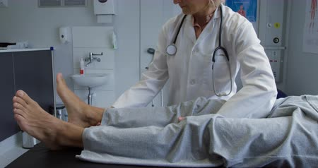 fysiotherapeut : Side view low section of a senior mixed race male patient lying on a couch while a Caucasian female doctor wearing a lab coat moves his leg up and down during a physiotherapy session Stockvideo
