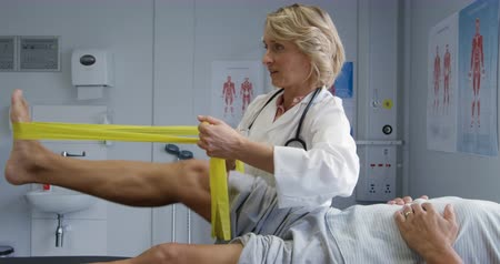 four legs : Side view low section of a senior mixed race male patient lying on a couch while a Caucasian female doctor wearing a lab coat holds a resistance band to exercise his leg with during a physiotherapy session