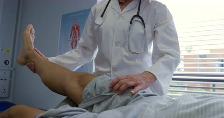 opção : Front view of a Caucasian female doctor wearing a lab coat exercising the leg of a senior mixed race male patient lying on a couch during a physiotherapy session at a hospital, slow motion Stock Footage