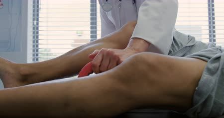 opção : Front view mid section of a Caucasian female doctor wearing a lab coat exercising the leg of a senior mixed race male patient lying on a couch using a foam roller during a physiotherapy session at a hospital, slow motion