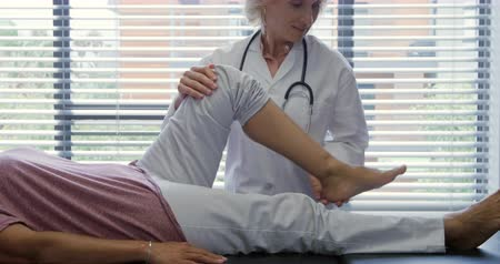 four legs : Front view of a Caucasian female doctor wearing a lab coat exercising the leg of a mixed race female patient lying on a couch during a physiotherapy session at a hospital Stock Footage