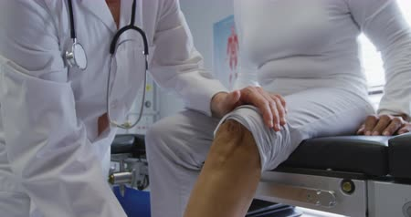 fysiotherapeut : Front view close up of a mixed race female patient sitting on a couch while a Caucasian female doctor wearing a lab coat holds her leg and exercises it during a physiotherapy session at a hospital, slow motion