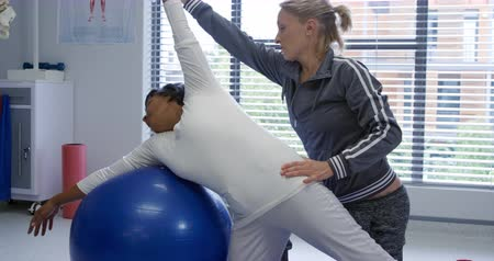 opção : Front view of a Caucasian female physiotherapist stretching a mixed race female patient leaning on an exercise ball during a physiotherapy session at a hospital
