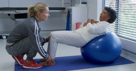 four legs : Side view of a Caucasian female physiotherapist helping a mixed race female patient exercise, holding her feet while she lies back on an exercise ball during a physiotherapy session at a hospital Stock Footage