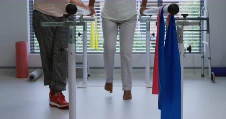 opção : Front view low section of a Caucasian female physiotherapist helping a mixed race female patient walk between parallel bars during a physiotherapy session at a hospital