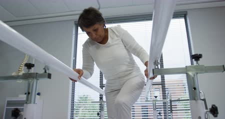 paralelo : Front view close up of a mixed race female patient walking between parallel bars during a physiotherapy session at a hospital, slow motion Vídeos