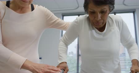 opção : Front view close up of a Caucasian female physiotherapist helping a mixed race female patient walk using a walking frame during a physiotherapy session at a hospital, slow motion