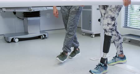 párhuzamos : Side view low section of a Caucasian female physiotherapist helping a Caucasian female patient with a prosthetic leg walk between parallel bars during a physiotherapy session at a hospital