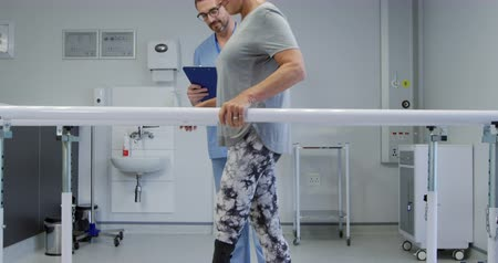 four legs : Side view low section of a Caucasian male physiotherapist making notes while a Caucasian female patient with a prosthetic leg walks between parallel bars during a physiotherapy session at a hospital, slow motion