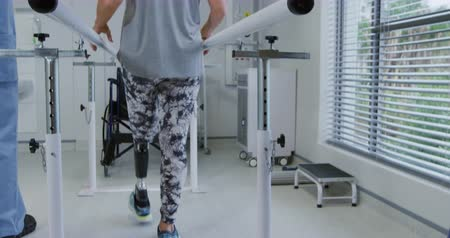 opção : Rear view of a Caucasian male physiotherapist helping a Caucasian female patient with a prosthetic leg walk between parallel bars during a physiotherapy session at a hospital, slow motion