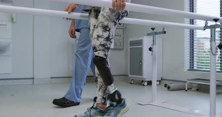 four legs : Side view low section of a Caucasian male physiotherapist helping a Caucasian female patient with a prosthetic leg walk between parallel bars during a physiotherapy session at a hospital, slow motion