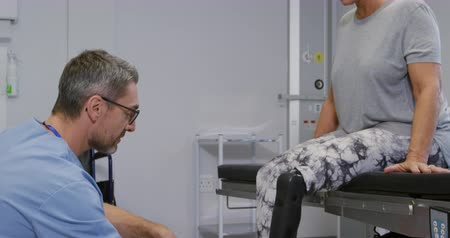 ajoelhado : Side view of a Caucasian male healthcare professional wearing glasses and scrubs kneeling and talking with a Caucasian female patient with a prosthetic leg, sitting on a couch in an examination room during a consultation session at a hospital