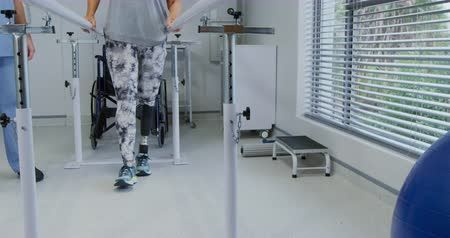 four legs : Front view of a Caucasian male physiotherapist helping a Caucasian female patient with a prosthetic leg walk between parallel bars during a physiotherapy session at a hospital, slow motion