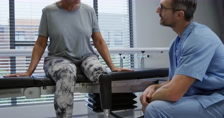 opção : Front view of a Caucasian male healthcare professional wearing glasses and scrubs talking with a Caucasian female patient with a prosthetic leg, sitting on a couch in an examination room during a consultation session at a hospital